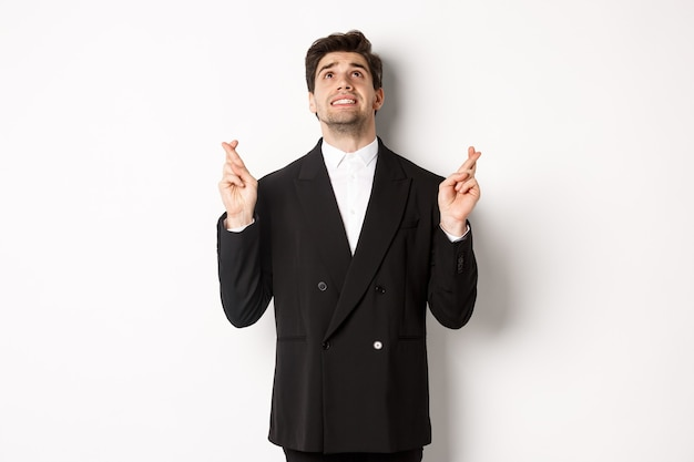 Portret van een gespannen en bezorgde knappe zakenman, vingers kruisend en omhoog kijkend, god smekend, een wens doend, staande tegen een witte achtergrond in zwart pak