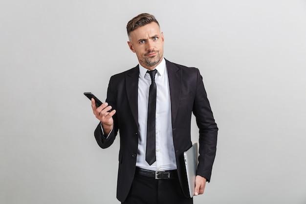 Portret van een gespannen, verbaasde volwassen zakenman in een kantoorpak met smartphone en laptop terwijl hij geïsoleerd staat