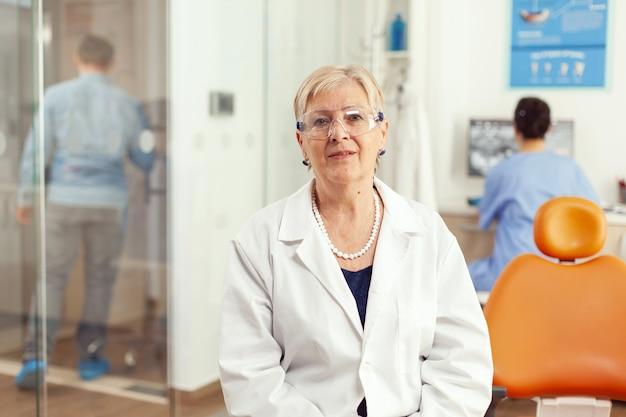 Portret van een gespecialiseerde senior tandartsvrouw in een stomatologisch kantoor terwijl een medisch assistent in gesprek is met de patiënt op de achtergrond