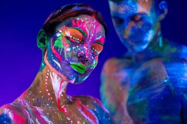 Portret van een gespierde man en vrouw geschilderd in ultraviolet poeder. body art gloeit in ultraviolet licht