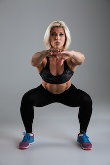 Portret van een gespierde volwassen sportvrouw die hurkzit doet