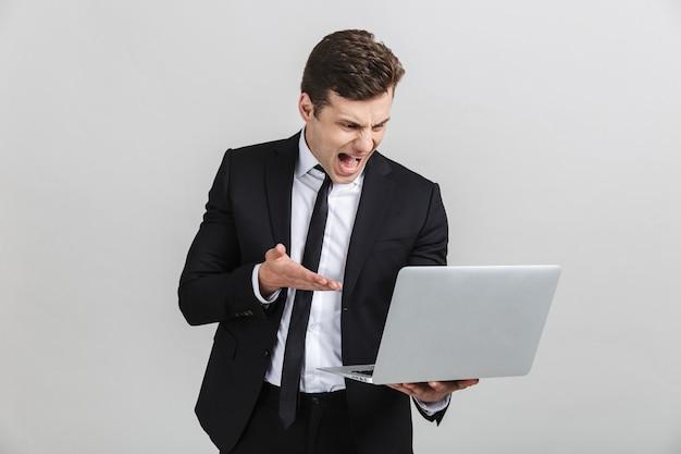 Portret van een gestresste, geïrriteerde jonge zakenman in een kantoorpak die schreeuwt terwijl hij zijn laptop geïsoleerd houdt