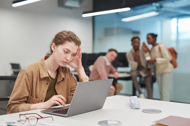 Portret van een gestresste jonge vrouw die een laptop gebruikt in een kantoor- of coworkingruimte met een groep mensen op de achtergrond, kopieer ruimte