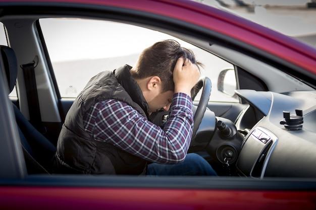 Portret van een gestresste man die op de stoel van de autobestuurder zit