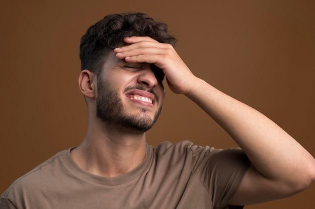 Portret van een gestresste man die zijn voorhoofd aanraakt
