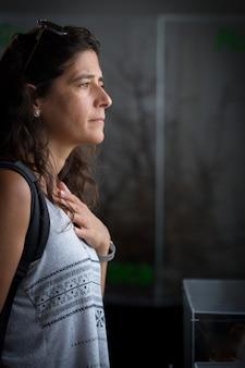 Portret van een gestresste mooie vrouw die haar borst aanraakt met een droevige uitdrukking of hartpijn heeft. aantrekkelijk model met pijn buitenshuis in huis