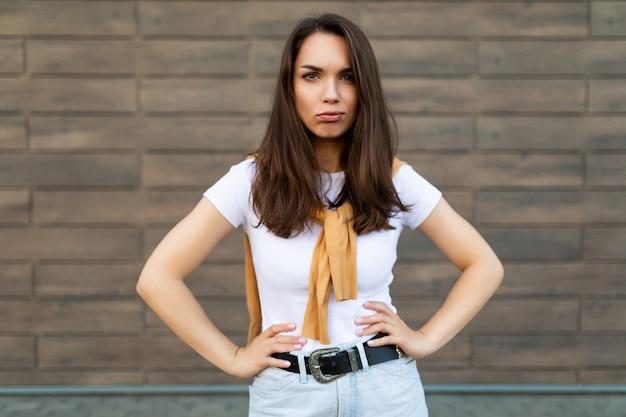 Portret van een gevoelige, verdrietige, beledigde, wrokkige jonge brunetvrouw met een casual wit t-shirt en een spijkerbroek met een gele trui in de buurt van een bruine muur op straat