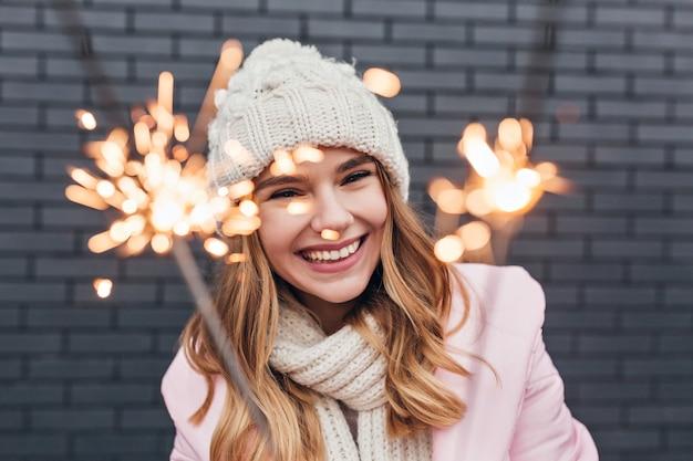 Portret van een geweldig vrouwelijk model dat bengalen licht met een glimlach bekijkt. mooie vrouw lachen in gebreide muts nieuwjaar vieren.