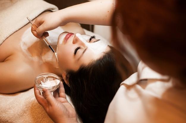 Portret van een geweldige brunette leunend op een spa-bed met gesloten ogen met een wit masker op haar gezicht en nek in een wellness-kuuroord.