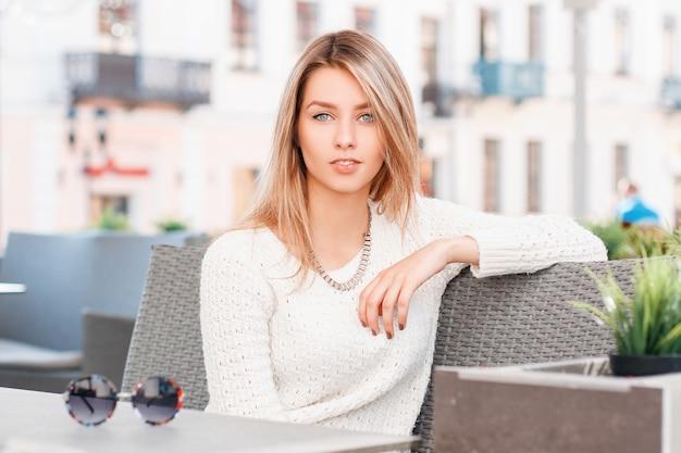 Portret van een geweldige vrolijke jonge vrouw met blauwe ogen met een lieve glimlach en blond haar met natuurlijke make-up in een gebreide trui op een terras. geweldig meisje.