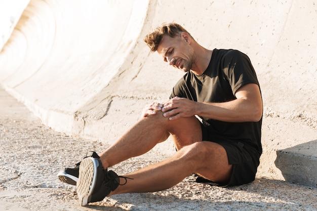 Portret van een gewonde sportman die aan kniepijn lijdt