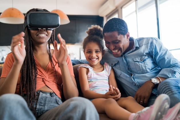 Portret van een gezin dat samen plezier heeft en videogames speelt met een vr-bril terwijl ze thuis blijven.