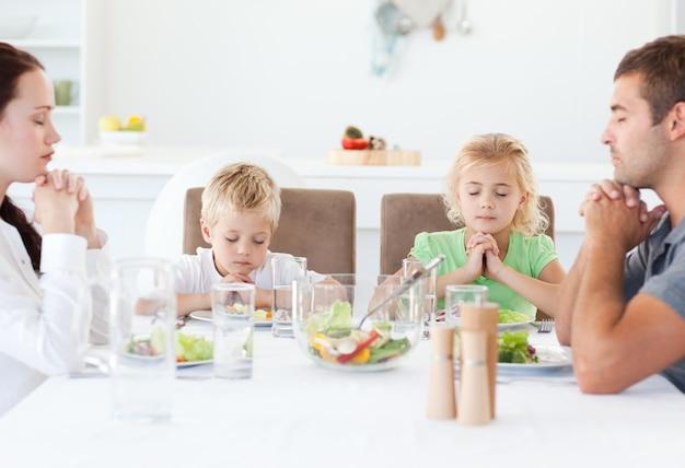 Portret van een gezin samen bidden tijdens de lunch