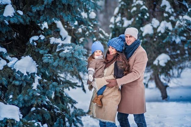 Portret van een gezin tegen de achtergrond van met sneeuw bedekte bomen