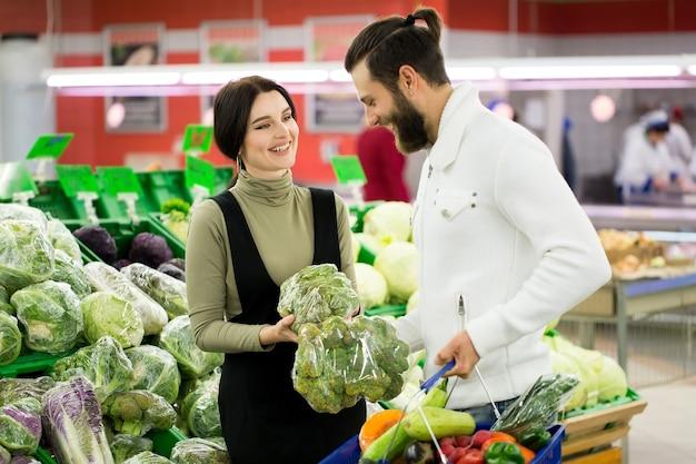 Portret van een gezond paar dat tijdens het winkelen groenten en fruit in de supermarkt bekijkt