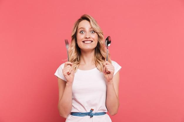 Portret van een gezonde blonde vrouw met een lichaamsmeetlint rond de taille met lepel en vork geïsoleerd over roze muur