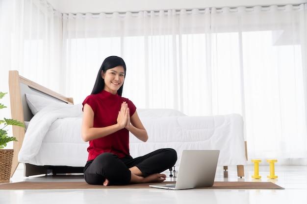 Portret van een gezonde jonge aziatische vrouw die yoga-oefeningen beoefent die in de slaapkamer zitten