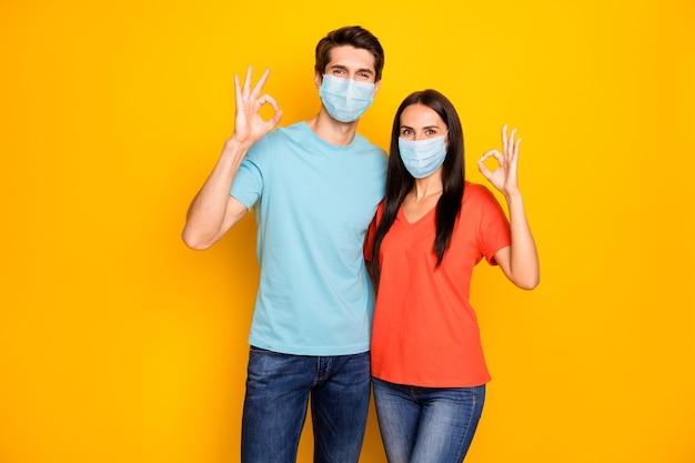 Portret van een gezonde vrouw die omhelst met een ok-teken met een veiligheidsmasker om infectie te stoppen