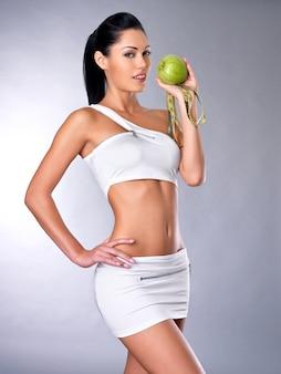 Portret van een gezonde vrouw met appel en een fles water. gezond fitness en eetlevensstijlconcept.