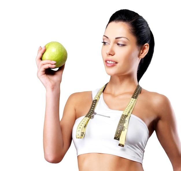 Portret van een gezonde vrouw met appel en een fles water.