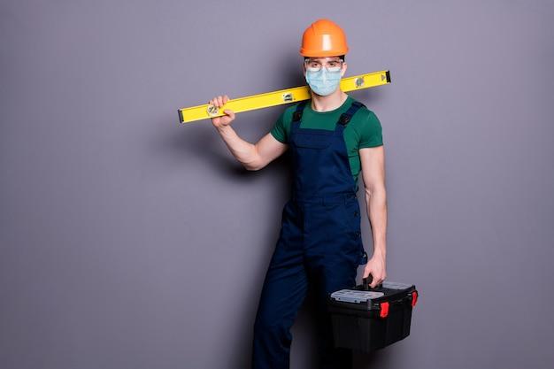 Portret van een gezonde werkman draagt een veiligheidsmaskerbril cov infectiepreventie met gereedschap