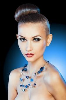 Portret van een glamoureus meisje met zwart haar en een dure ketting met kostbare en gekleurde stenen