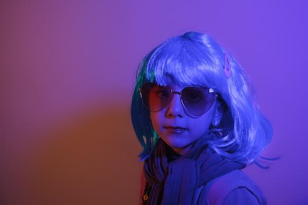Portret van een glamourmeisje met een kleurrijke pruik op een paarse achtergrond