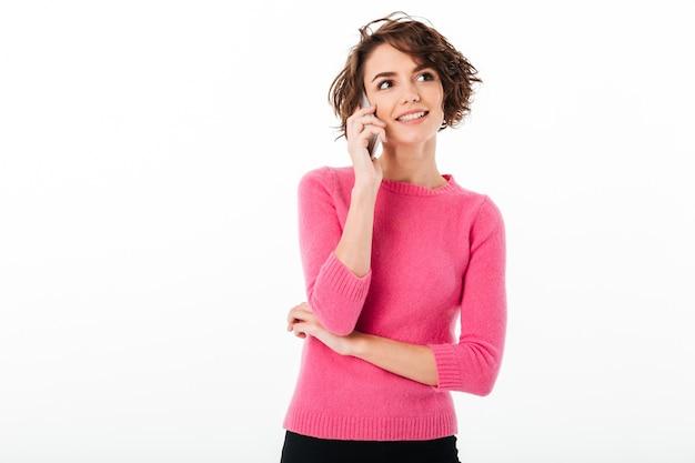 Portret van een glimlachend aantrekkelijk meisje dat op mobiele telefoon spreekt