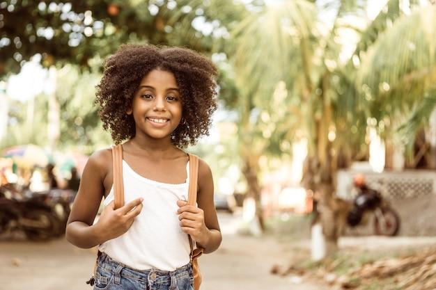 Portret van een glimlachend afro-amerikaans meisje dat met handen een rugzak vasthoudt terug naar schoolconcept