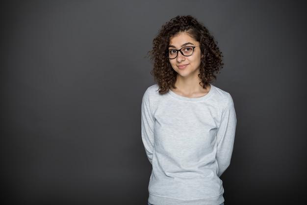 Portret van een glimlachend donkerbruin meisje in glazen op een zwarte achtergrond