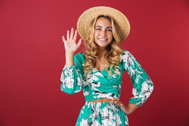 Portret van een glimlachend gelukkig jong blond meisje in een felblauwe jurk die zich voordeed over een rode muur die naar je zwaait met een hoed?
