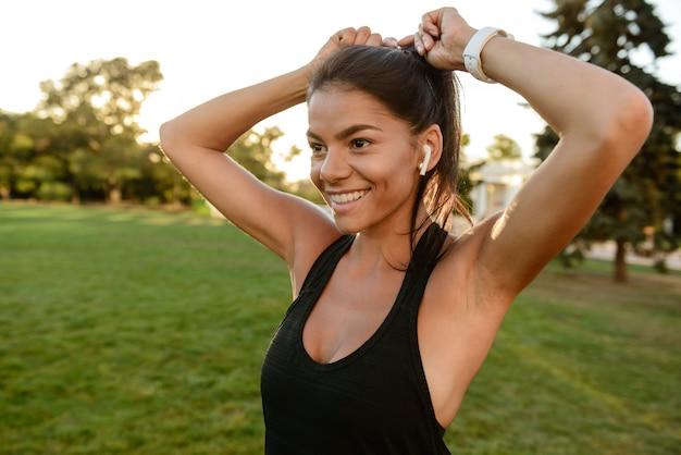 Portret van een glimlachend geschiktheidsmeisje dat in oortelefoons haar haar bevestigt