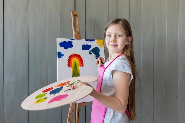 Portret van een glimlachend het holdingspalet van het blondemeisje in hand schilderen op de schildersezel met verfborstel