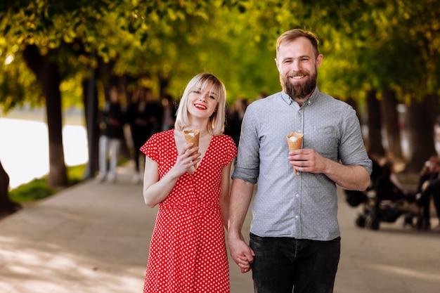 Portret van een glimlachend hipsterspaar dat roomijs eet en pret in de stad heeft. stijlvolle jonge man met baard en blonde vrouw in rode jurk lopen in de straat