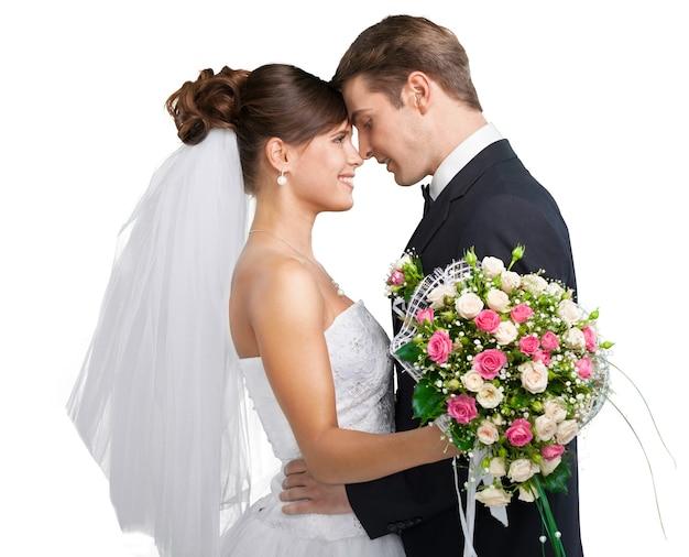 Portret van een glimlachend jong huwelijkspaar dat op witte achtergrond wordt geïsoleerd
