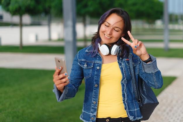 Portret van een glimlachend jong meisje die selfie foto in park maken