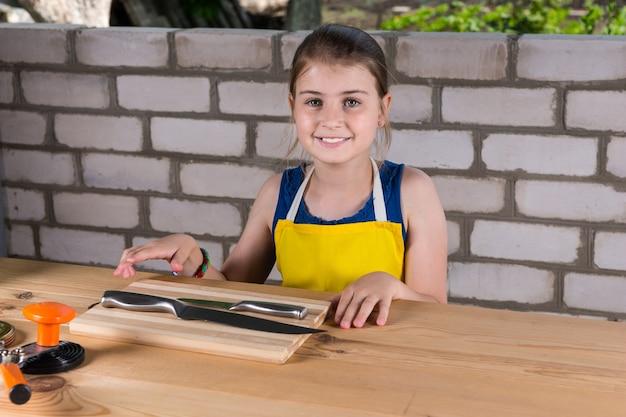 Portret van een glimlachend jong meisje met een schort, zittend aan een houten tafel met messen en conservenbenodigdheden