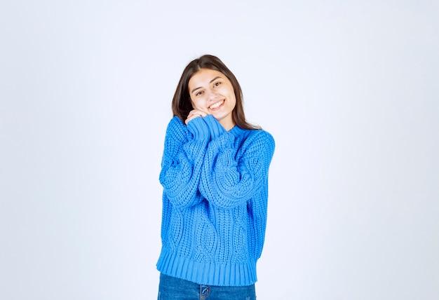 Portret van een glimlachend jong meisjesmodel dat staat en ernaar uitkijkt.