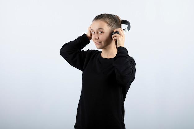 Portret van een glimlachend jong meisjesmodel die hoofdtelefoons in handen houdt