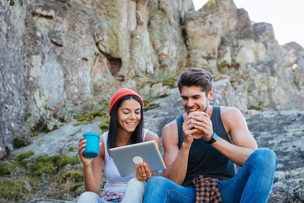 Portret van een glimlachend jong stel dat een pauze heeft van wandelen en tabletcomputer gebruikt