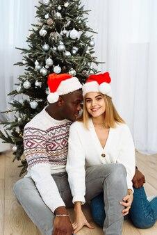 Portret van een glimlachend jong stel zit in de buurt van de kerstboom en viert samen nieuwjaar. gelukkige man en vrouw genieten van wintervakantie in de buurt van versierde dennenboom