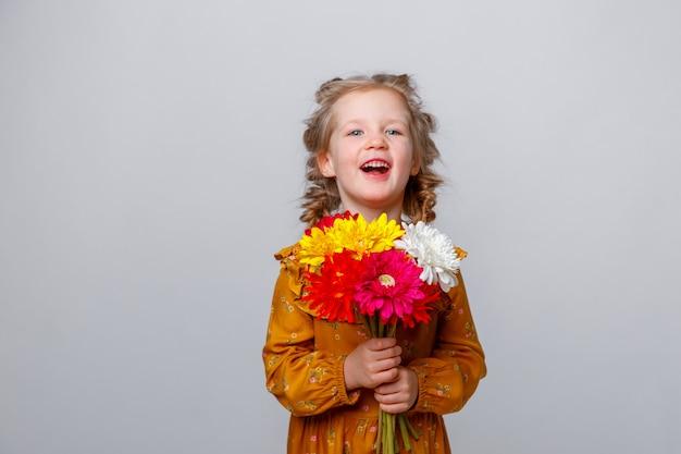 Portret van een glimlachend kind een geïsoleerd blondemeisje met een boeket van bloemen