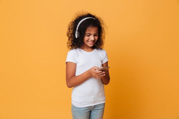 Portret van een glimlachend klein afrikaans meisje dat aan muziek luistert