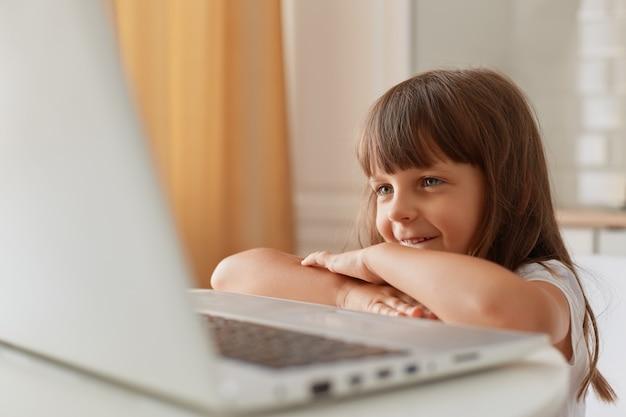 Portret van een glimlachend klein donkerharig vrouwelijk kind dat aan tafel zit voor een laptopcomputer en glimlacht, een klein kleutermeisje dat tekenfilms of online les kijkt.