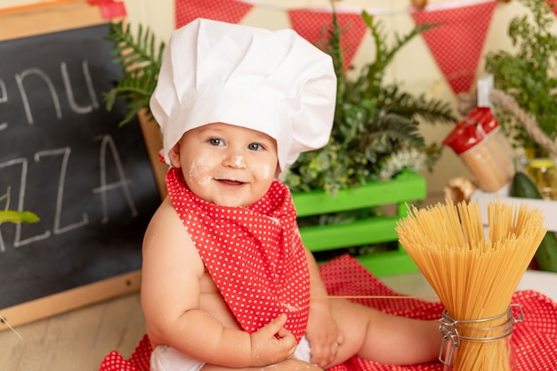 Portret van een glimlachend klein kind in een koksmuts die spaghetti in de keuken voorbereidt