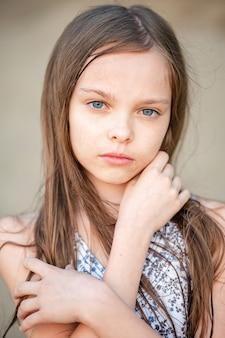 Portret van een glimlachend klein mooi meisje met lang haar. meisje 7-9 jaar oude handen op het gezicht. jeugd, frisheid.