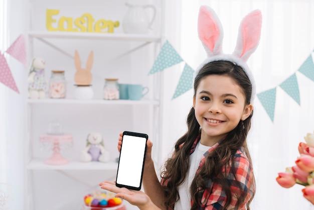 Portret van een glimlachend meisje dat het nieuwe smartphonescherm op pasen-dag toont