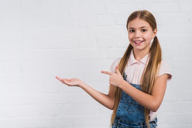Portret van een glimlachend meisje dat iets voorstelt tegen witte bakstenen muur
