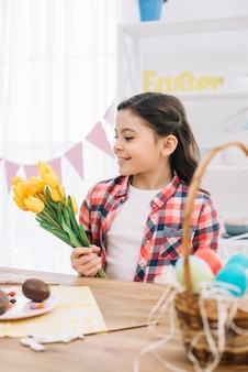 Portret van een glimlachend meisje die gele tulpenbloemen op pasen-dag houden