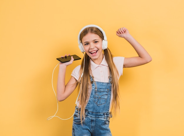 Portret van een glimlachend meisje die van de muziek op hoofdtelefoon door mobiele telefoon genieten die tegen gele achtergrond dansen